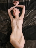 Kate completely naked on black sheets.
